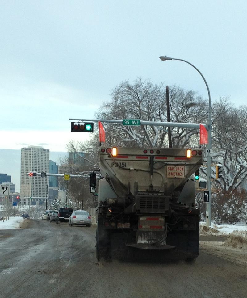 Camion répendeur de sable sur la neige.